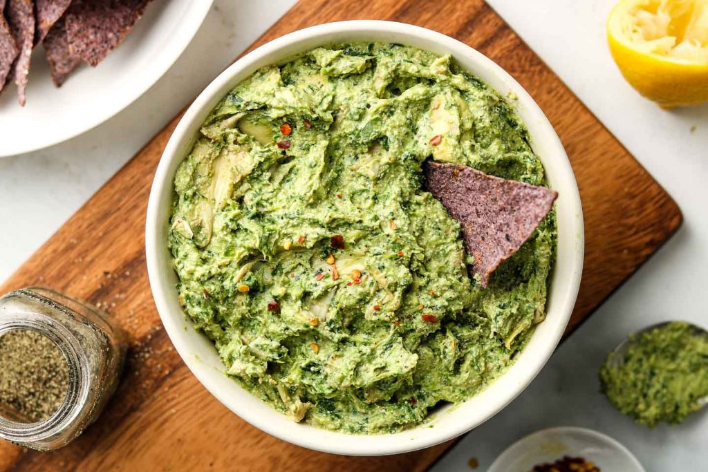Avocado Spinach Artichoke Dip on a wood board with chip inside