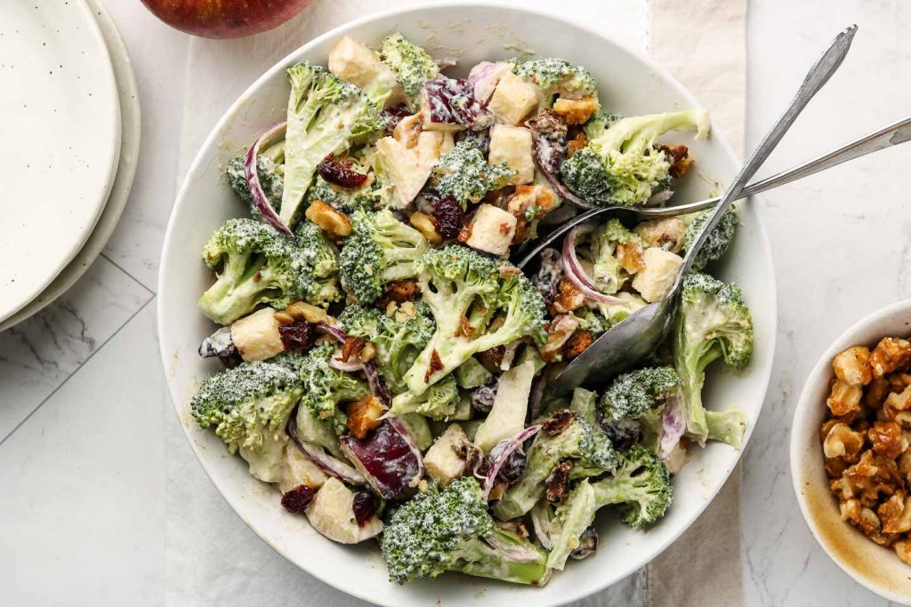 vegan broccoli salad with apples, onions, walnuts, cranberries vegan bacon in a serving bowl