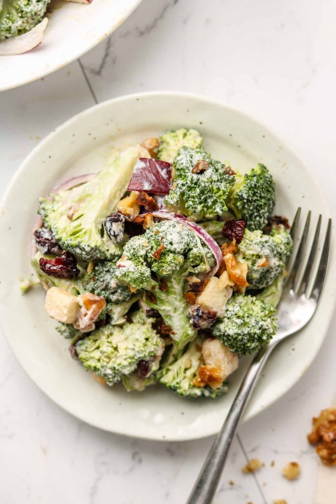 vegan crunchy broccoli salad with dairy free dressing on a serving plate close up shot