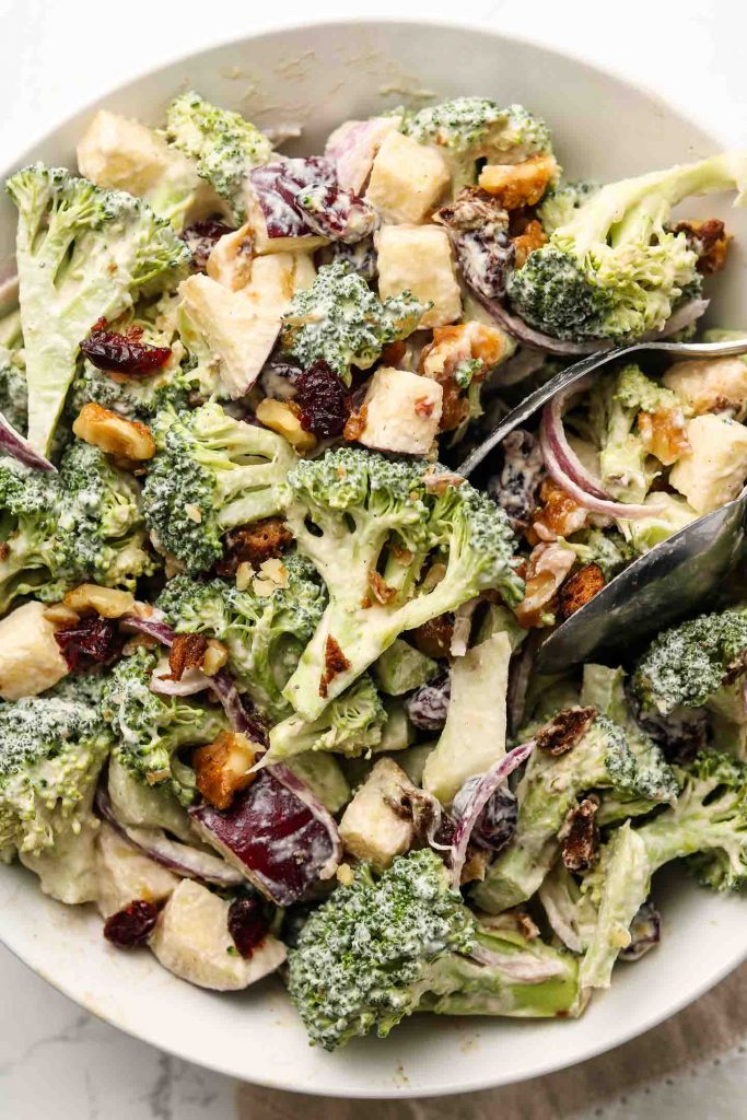 vegan crunchy broccoli salad with dairy free dressing in a shallow bowl close up shot