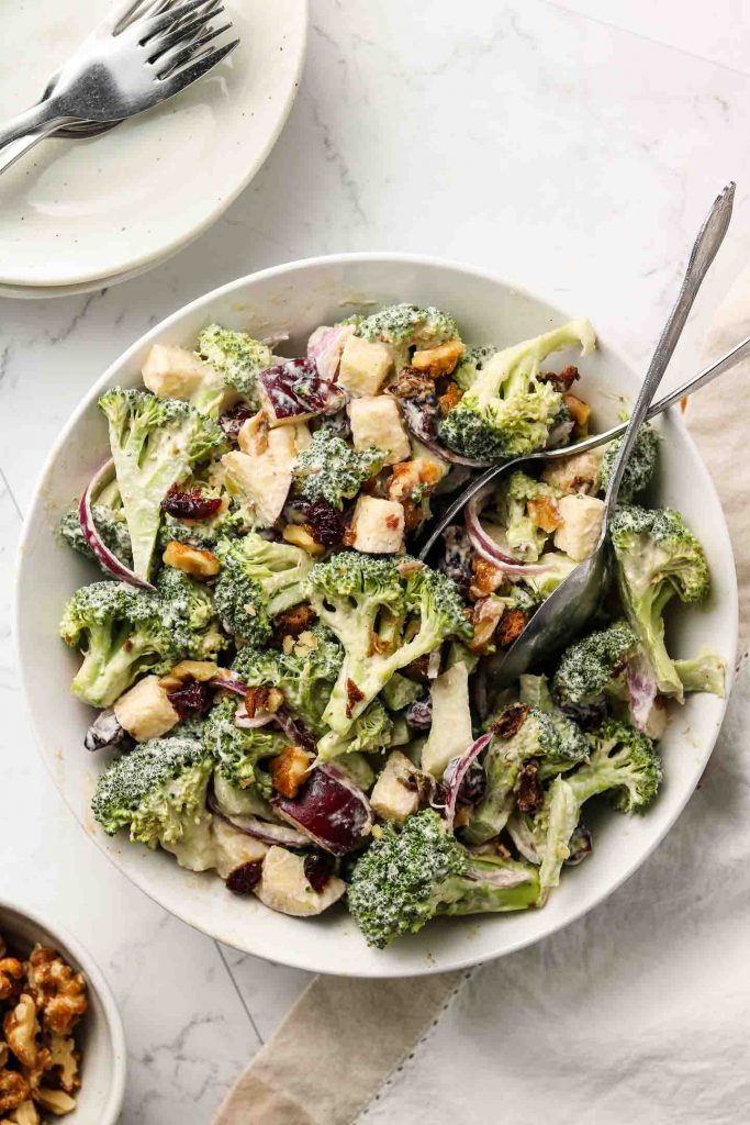 dairy free crunchy broccoli salad with apples, onions, walnuts, cranberries vegan bacon in a serving bowl with spoons