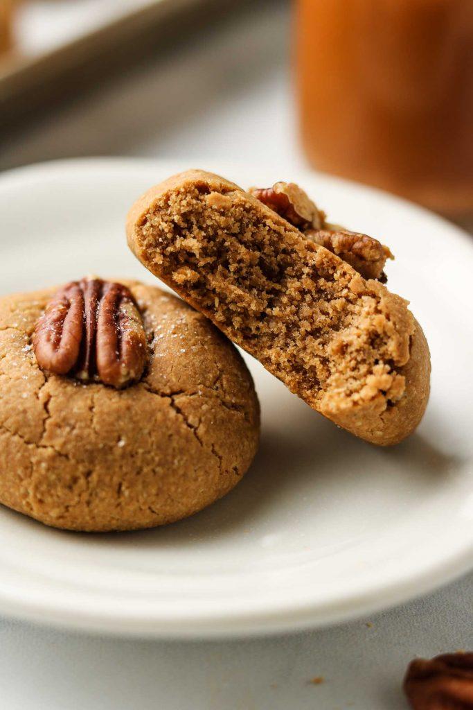 vegan browned coconut butter maple pecan cookies on a plate bitten