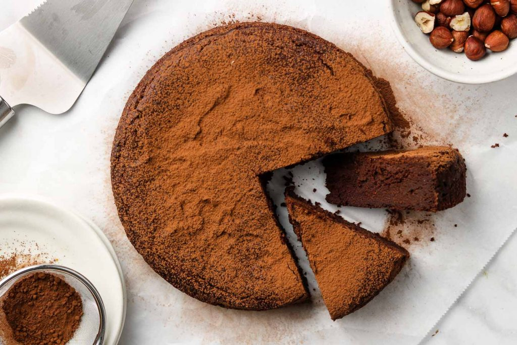 vegan flourless chocolate rum cake on parchment paper cut into two slices