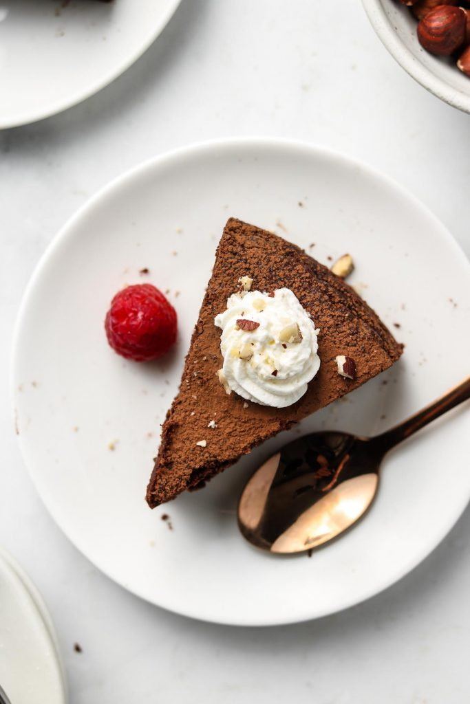 sliced hazelnut flourless chocoalte cake with whip cream