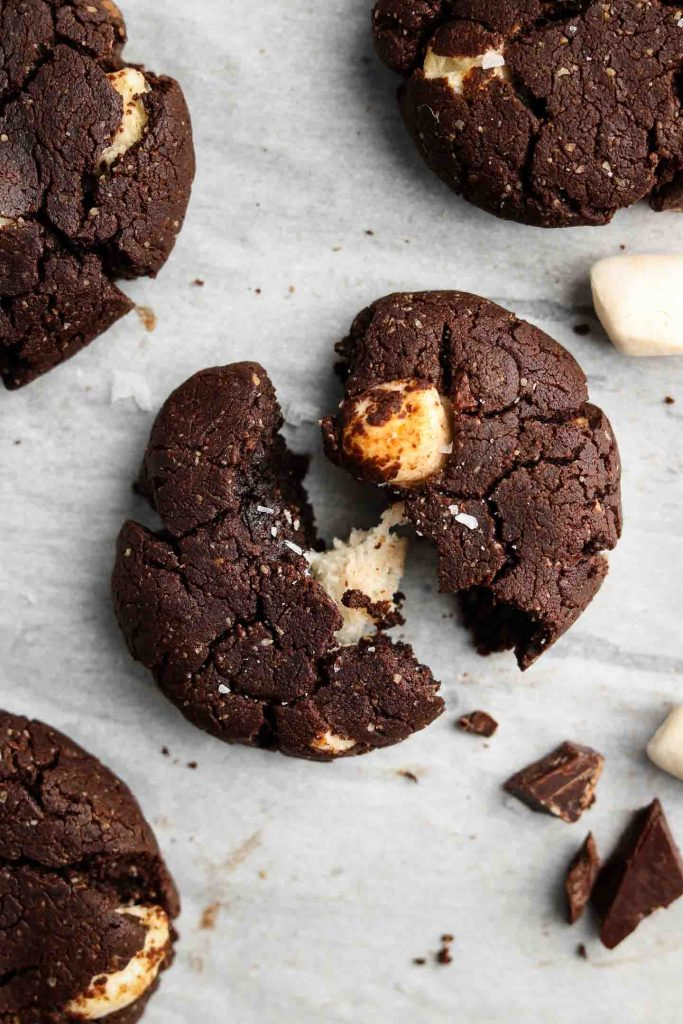 vegan peppermint double chocolate cookies with marshmellows cut in half on parchment paper