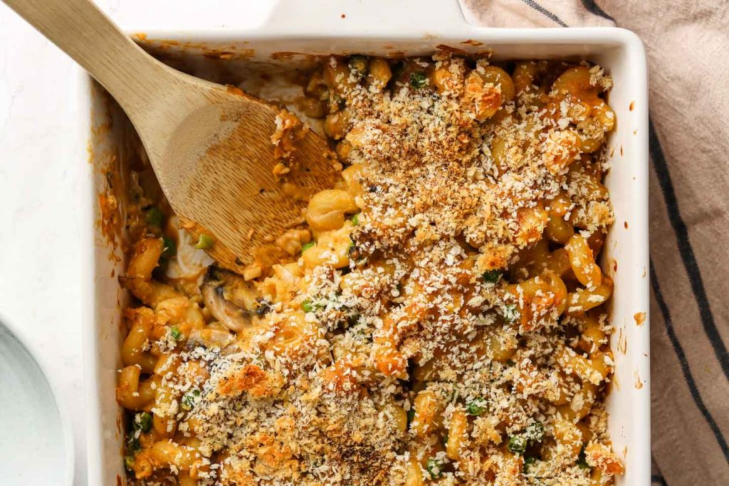 vegan tuna noodle casserole in a baking dish with wooden spoon landscape photo