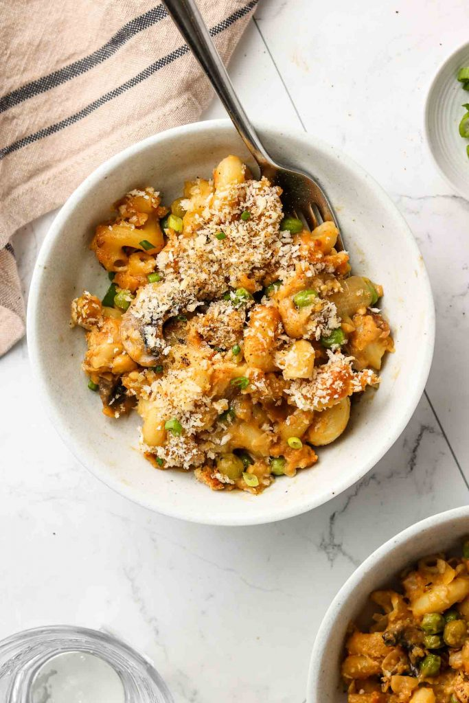 vegan tuna noodle casserole in a bowl with breadcrumbs and a fork