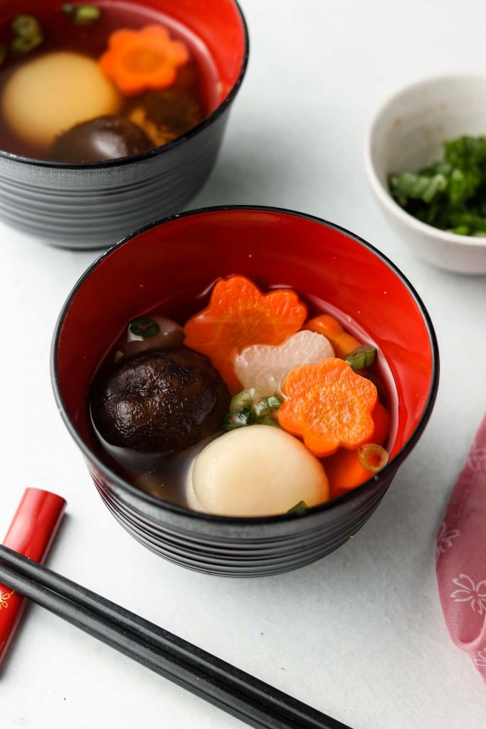kanto ozoni in a bowl with mochi rice cakes, shiitake mushrooms, flower carrots and flower daikon