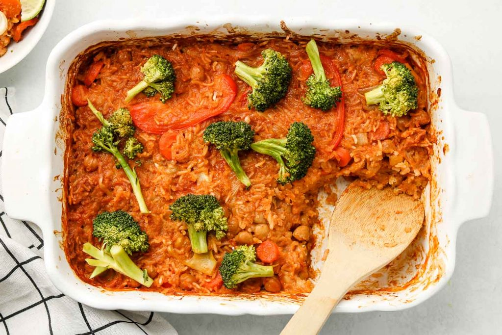 rice casserole with curry sauce and broccoli on top in baking dish