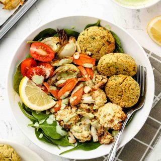 baked falafel balls on a warm salad with cilantro sauce on top