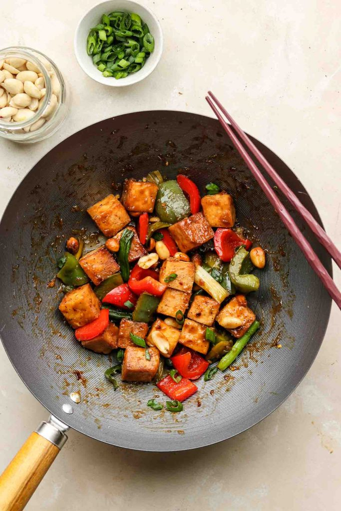 asian vegan stir fry in a wok with tofu and bell peppers