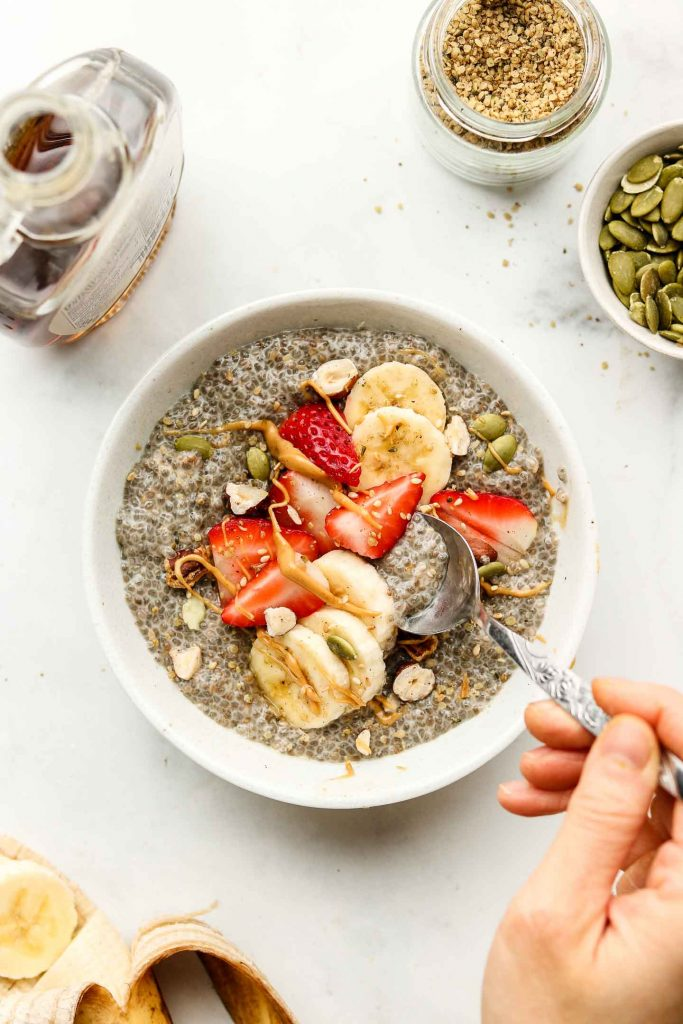 hand spooning out chia pudding from a white bowl