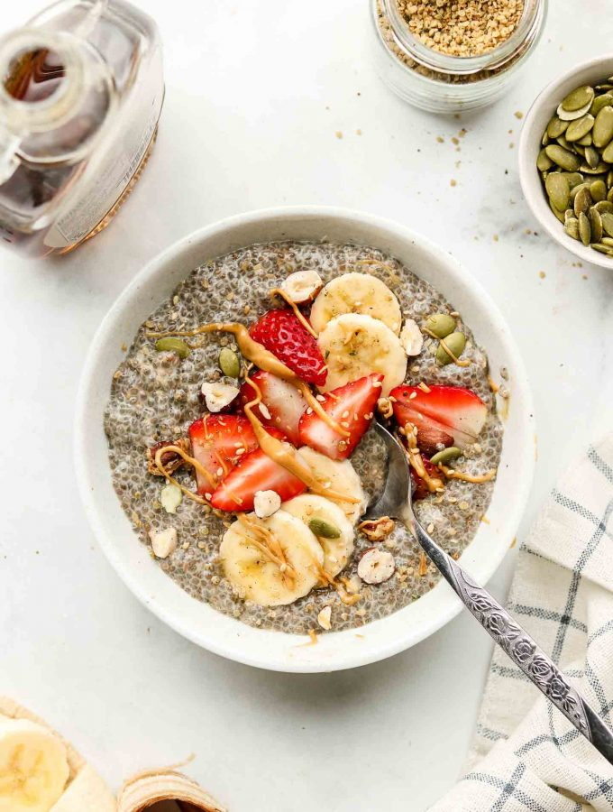 chia seed pudding in a white bowl with strawberries, bananas, nuts and peanut butter on top on a marble counter top