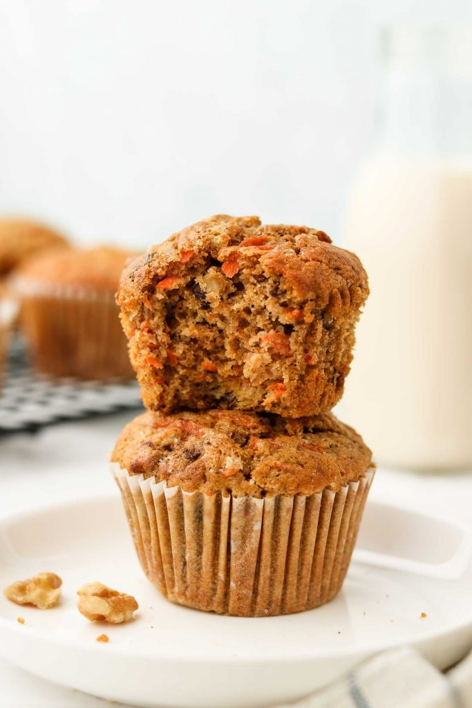 vegan carrot muffins stacked with a bite shot