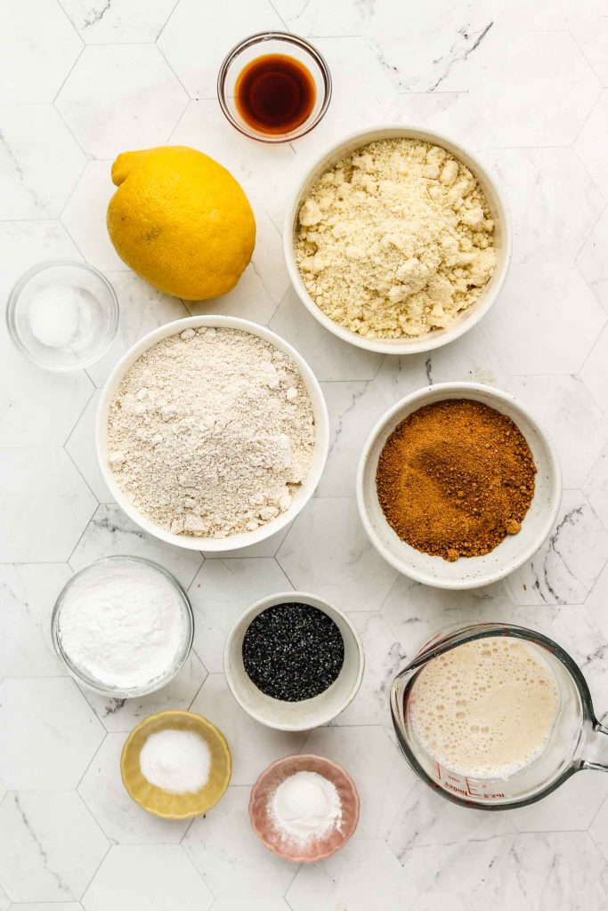 ingredients for vegan lemon poppy seed muffins on a marble backdrop