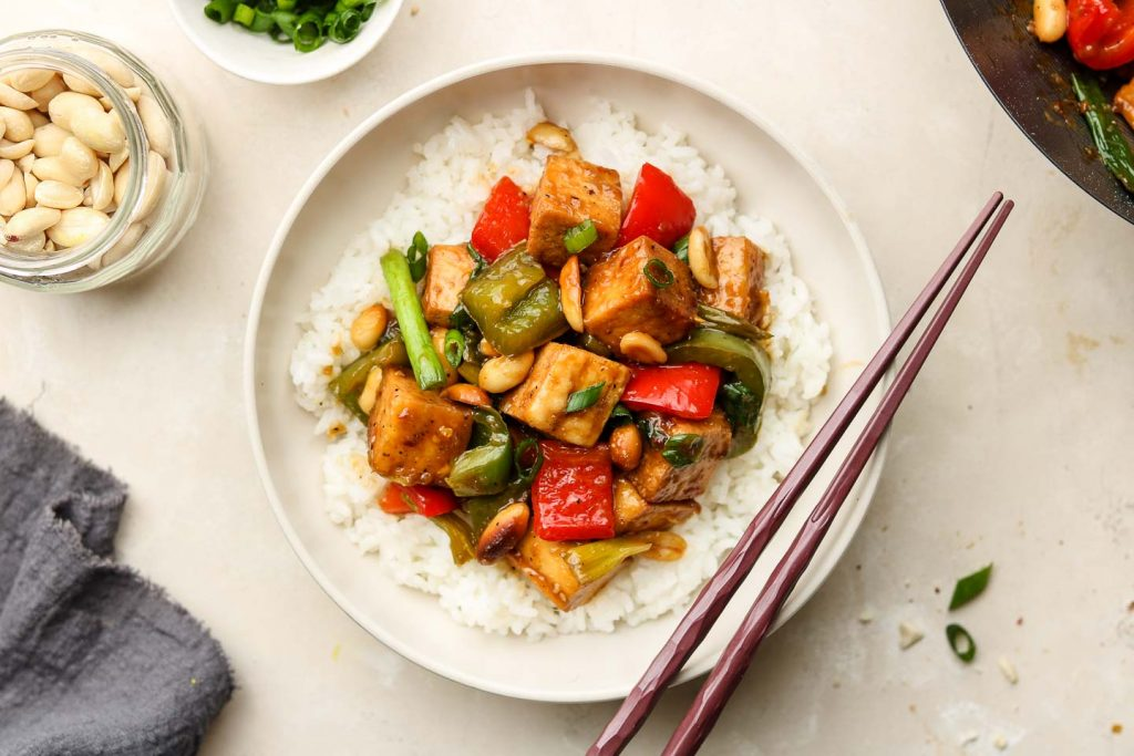 white rice with kung pao tofu on top in a bowl