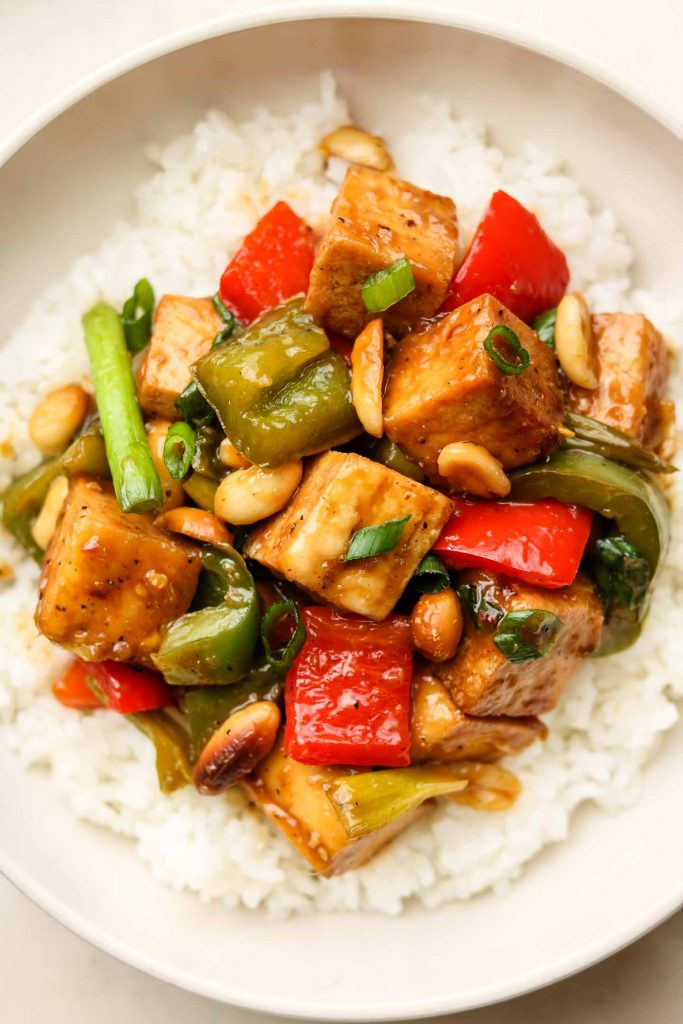 close up shot of spicy tofu stir fry with vegetables on top of rice in a bowl