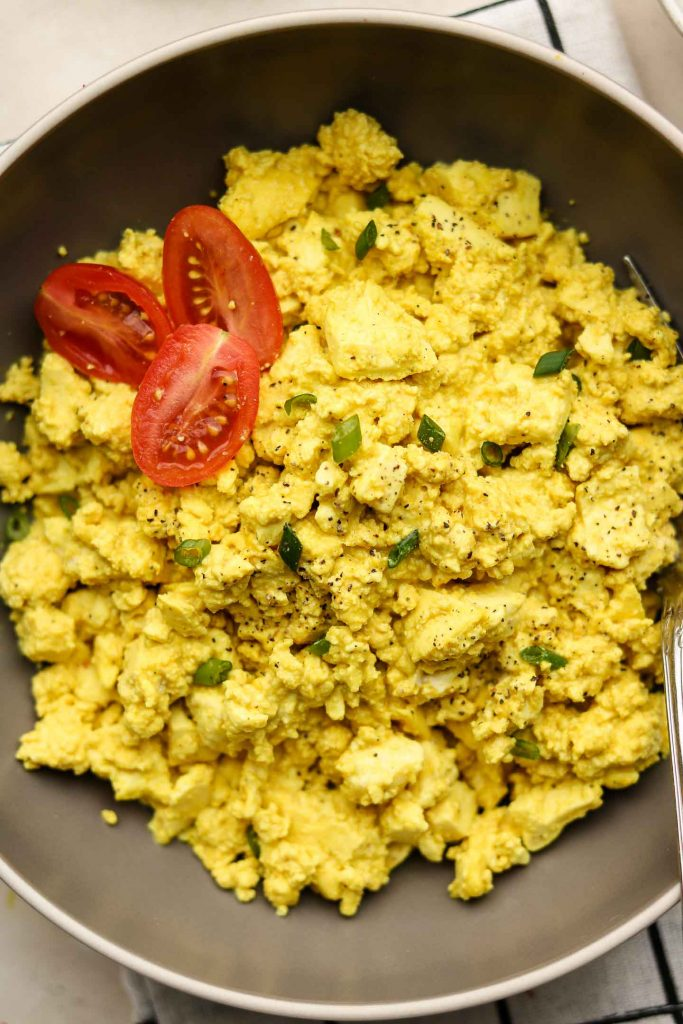 tofu scramble in a brown bowl close up shot with cherry tomatoes and green onions on top