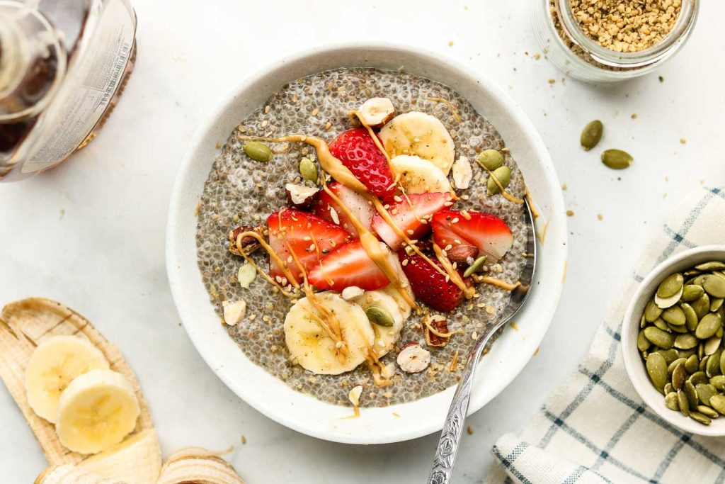 chia seed pudding in a white bowl with strawberries, bananas, nuts and peanut butter on top