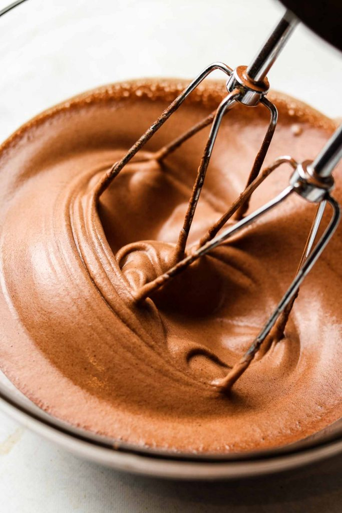 whipping aquafaba and cocoa powder in a bowl