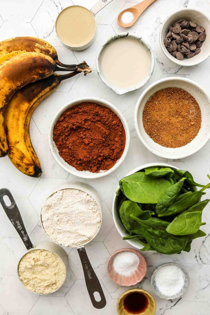 ingredients for green smoothie banana chocolate muffins on a marble top