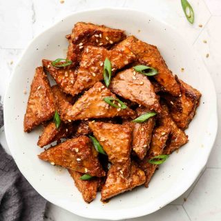 peanut tempeh in a white bowl with scallions on top