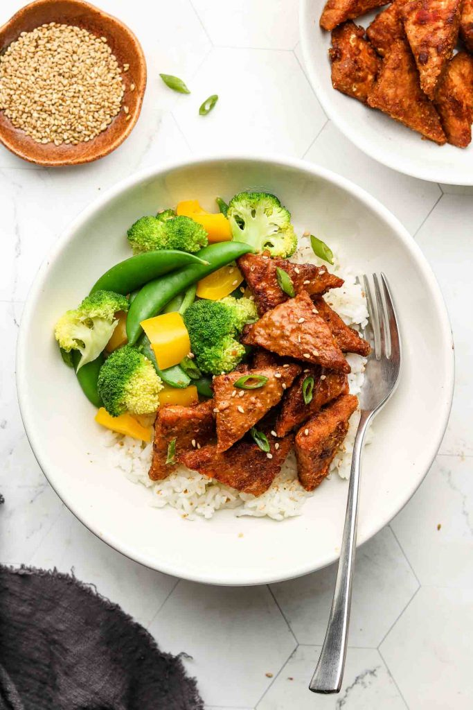 marinated peanut tempeh in a rice bowl with vegetables