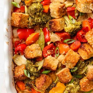 rice, tempeh and vegetables covered in sesame ginger sauce in casserole dish