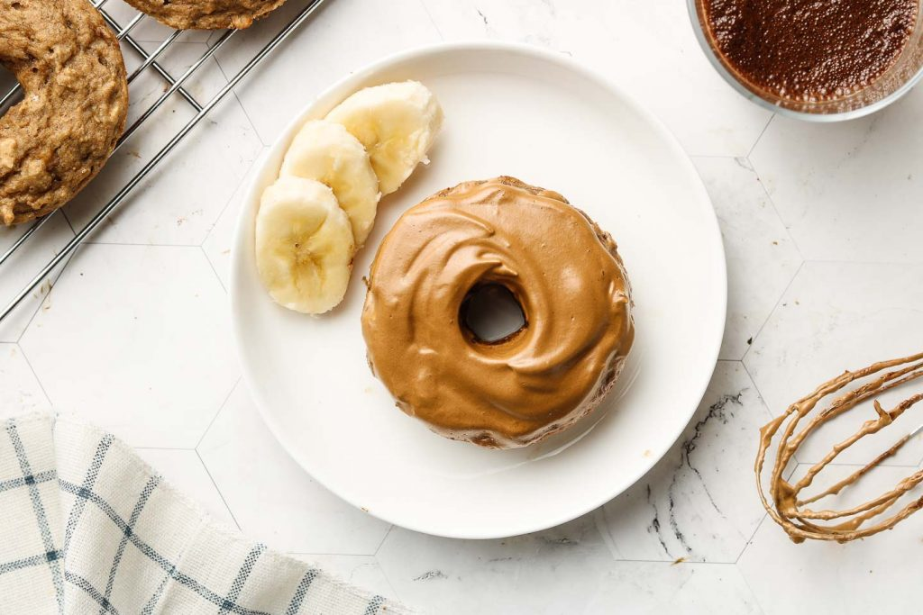 baked donut with coffee whip on top and bananas on a white plate