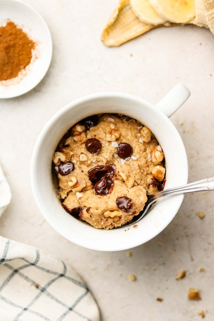 banana bread mug cake with chocolate chips and walnuts on top