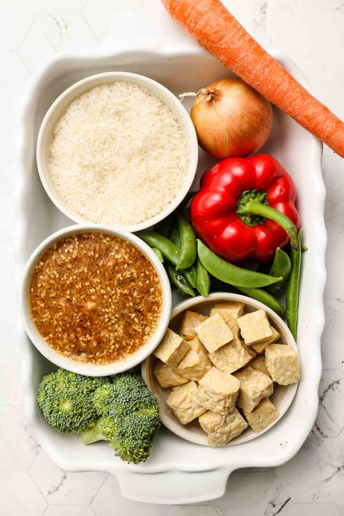 ingredients for vegan tempeh rice casserole in a baking dish
