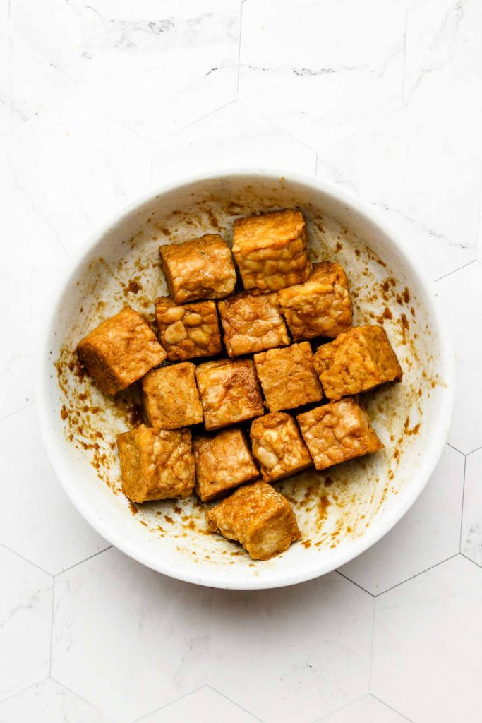 cubed tempeh marinating in smoky sauce