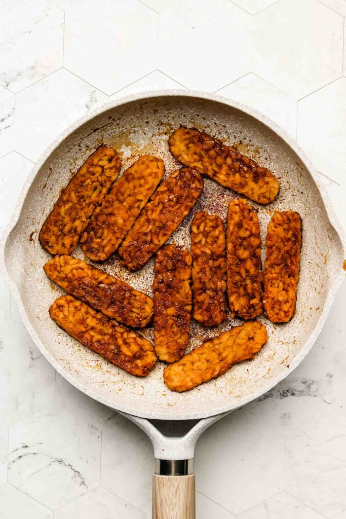 tempeh in a fry pan with smoky marinade cooked