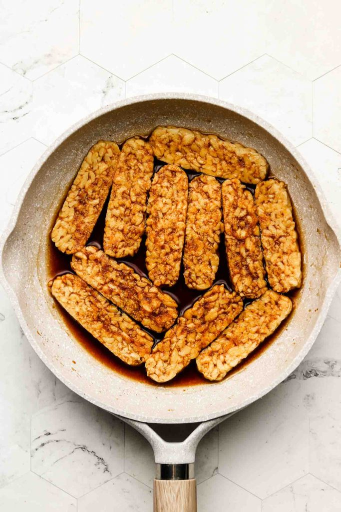 tempeh in a fry pan with smoky marinade