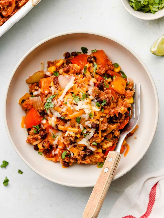 quinoa mexican taco casserole in a white bowl with dairy free cheese on top