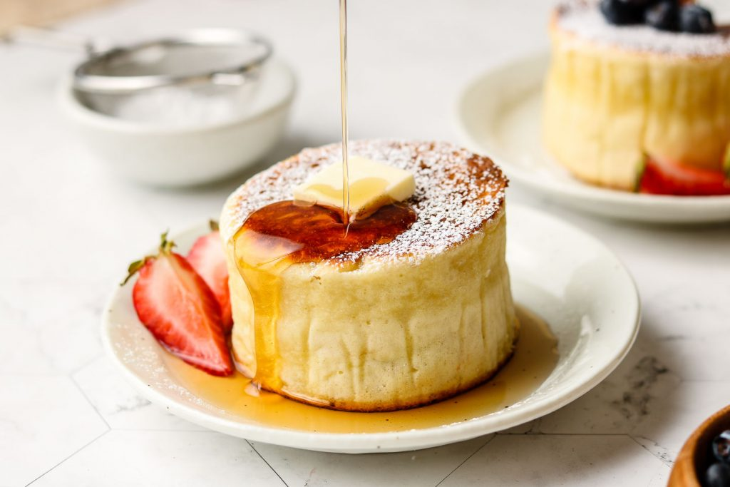 thick and fluffy pancakes on a plate with butter on top