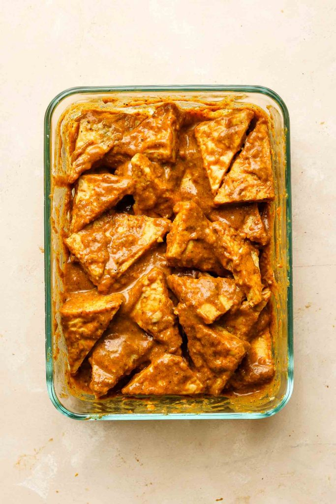 triangle tempeh pieces marinating in satay sauce