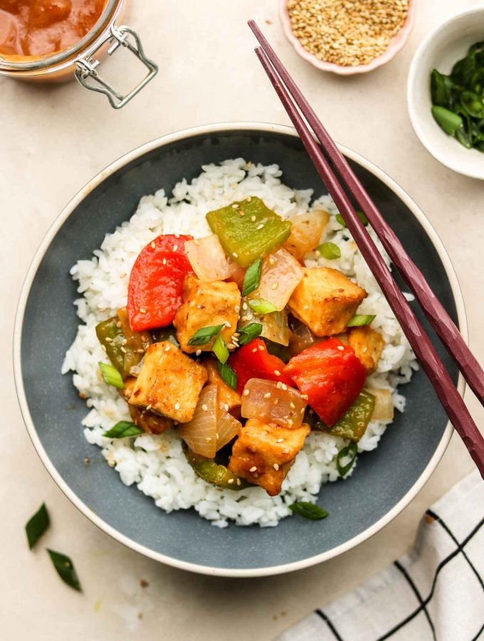 sweet and sour sauce with tofu bell pepper and onion over rice in blue bowl