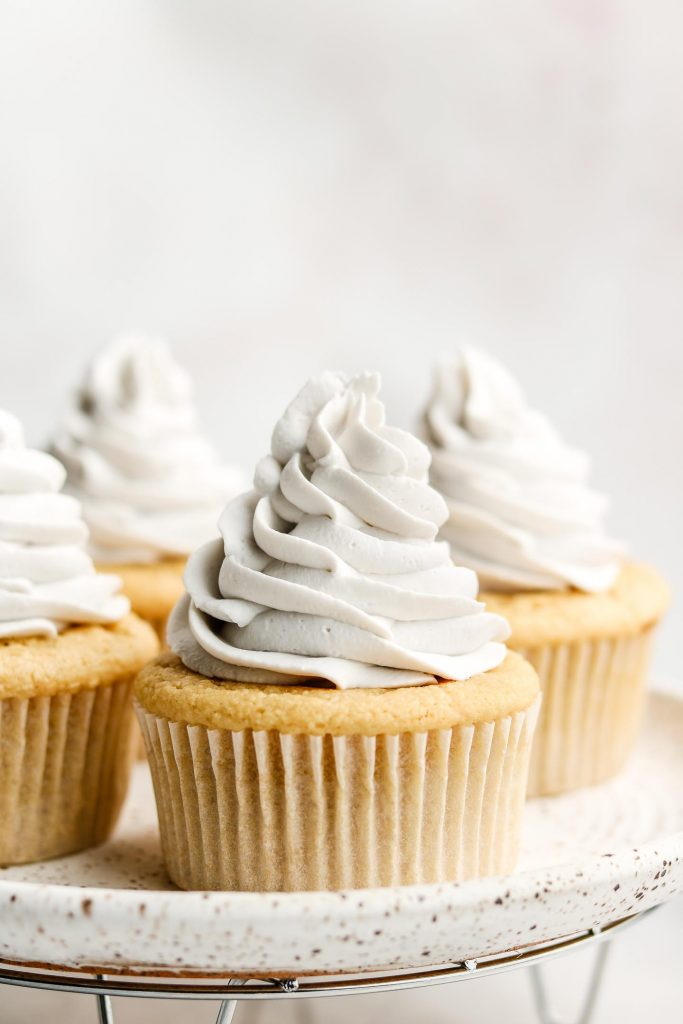 vanilla cupcakes with coconut whip cream frosting on a white plate