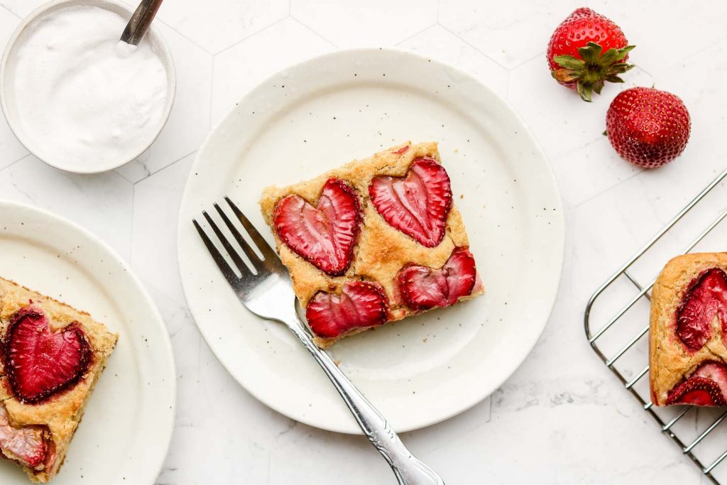 strawberry lemon snack cake on a speckled white plate with a fork