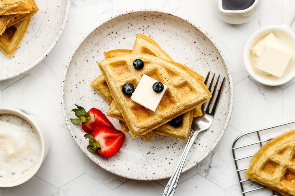oatmeal waffles on a speckled white plate with non dairy butter, blueberries and strawberries on top