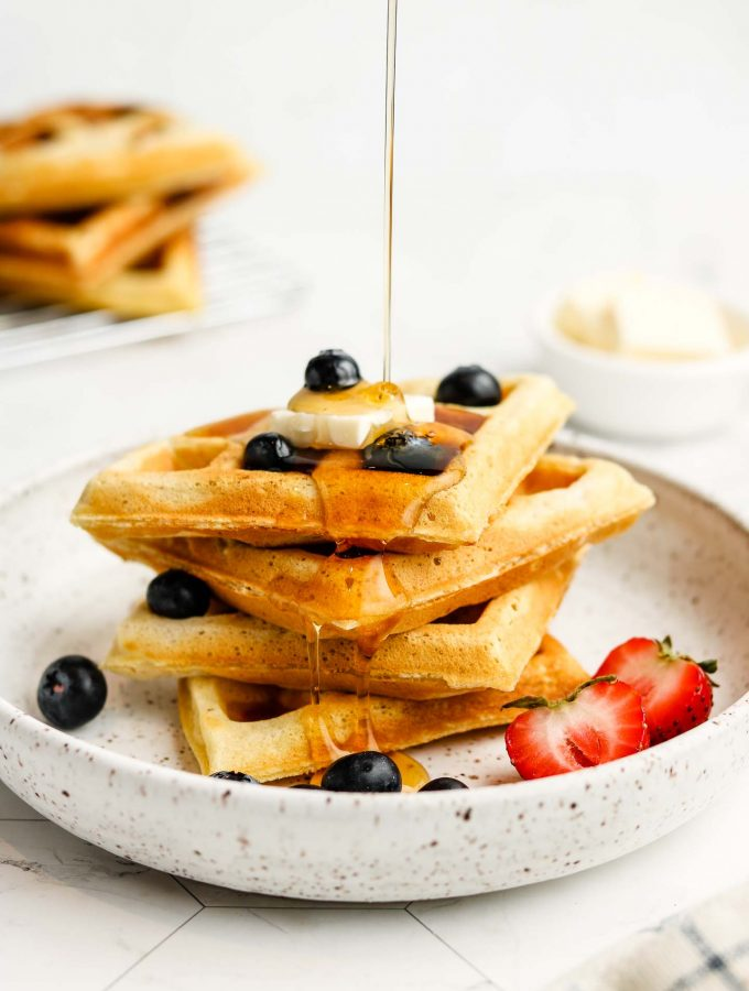 maple syrup pour shot on oat flour waffles with vegan butter and blueberries