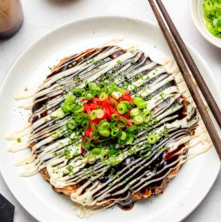 vegan okonomiyaki on a white plate with mayonnaise and scallions on top
