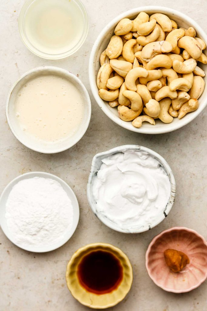 ingredients for cashew buttercream in bowls on a beige back drop
