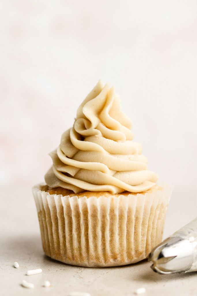 head shot of vanilla cupcake with vegan buttercream swirled on top and a piping tip beside it