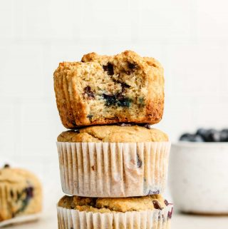 3 chocolate chip blueberry muffins stacked on each other with a bowl of blueberries in the background