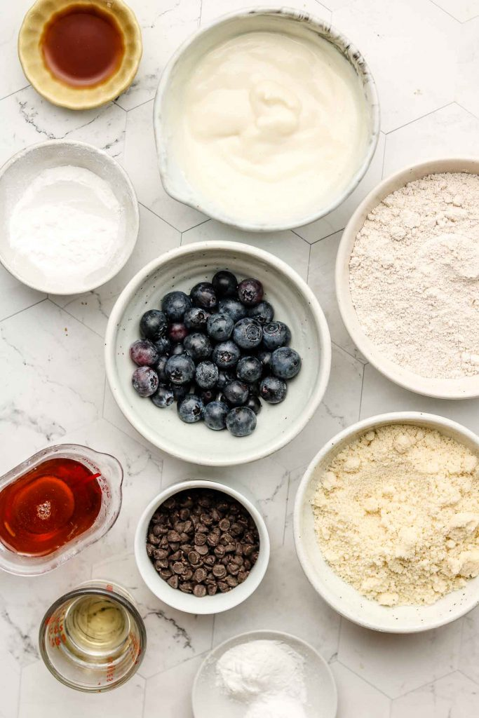ingredients for blueberry chocolate chip muffins in bowls on top of a marble back drop