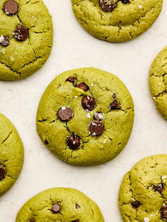 baked vegan matcha cookies with chocolate chips and flaky salt on a beige tile