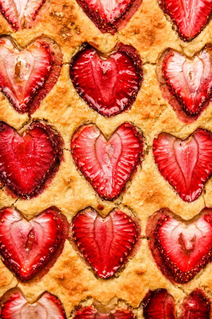 close up shot of lemon snack cake with strawberries on top