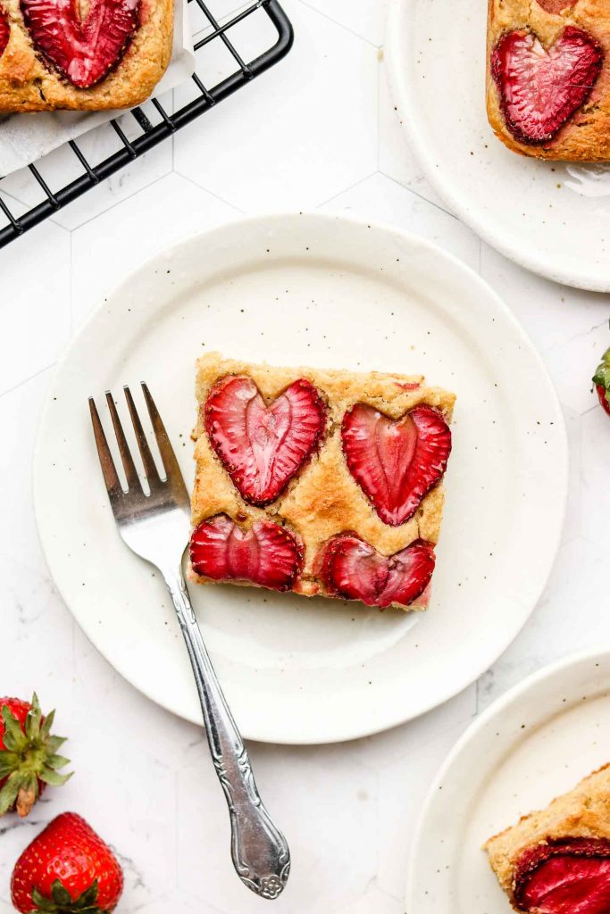 square piece of lemon sheet cake with strawberries on top on a white speckled plate and a fork on the side